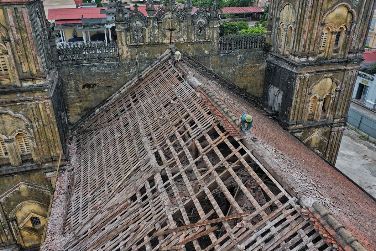 Chiều 19/7, thợ đang dỡ mái ngói nhà thờ Bùi Chu. Ảnh: Giang Huy.