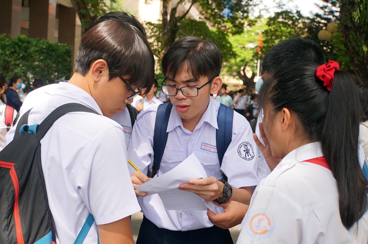 Nam sinh trao đổi với bạn cùng trường sau giờ thi Toán cơ bản, trường Phổ thông Năng khiếu (Đại học Quốc gia TP HCM) ngày 11/7. Ảnh: Mạnh Tùng.