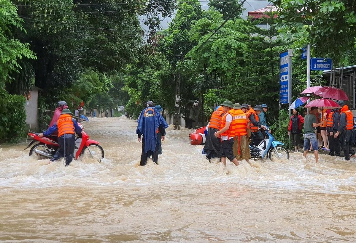 Lực lượng cứu hộ giúp người dân ở những đoạn ngập sâu, nước chảy xiết. Ảnh: Lê Mạnh.