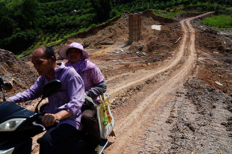 Người dân đi qua một con đập bị vỡ sau trận mưa lớn tại hồ chứa Sa Tử Khê ở huyện Dương Sóc hôm 16/7. Ảnh: Reuters.