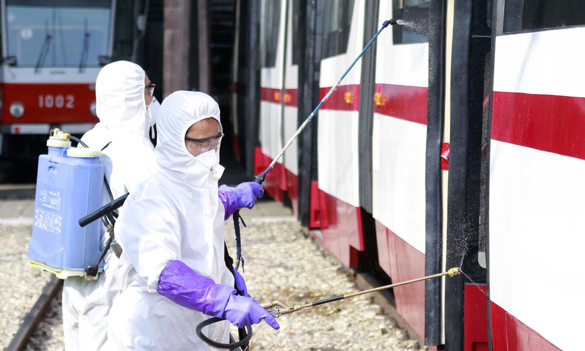 Nhân viên y tế tẩy trùng một toa tàu tại nhà ga Songsam ở thủ đô Bình Nhưỡng hồi cuối tháng hai. Ảnh: AP.