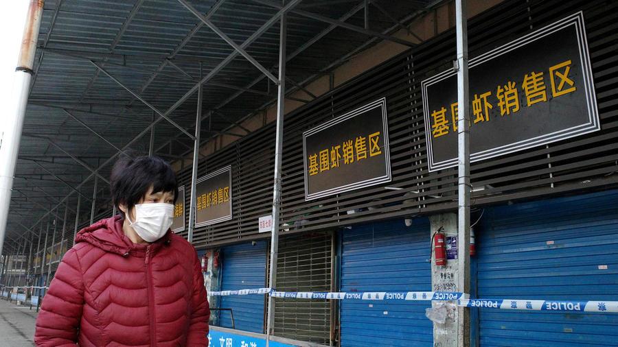 Một phụ nữ đi ngang chợ hải sản Hoa Nam ở Vũ Hán, Trung Quốc, khi nó bị đóng cửa hồi tháng một. Ảnh: AFP.