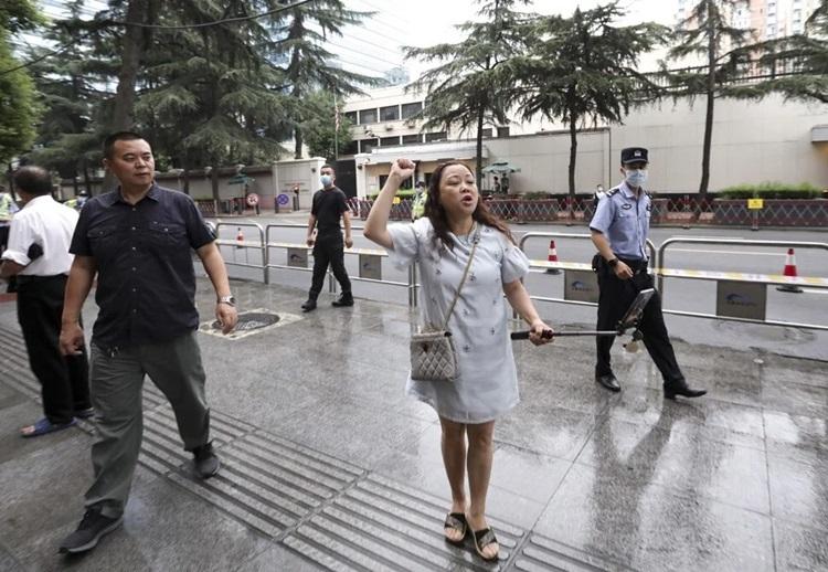 Người phụ nữ đứng hát bài Tôi yêu Trung Quốc trước Tổng lãnh sự quán Mỹ hôm nay. Ảnh: SCMP.