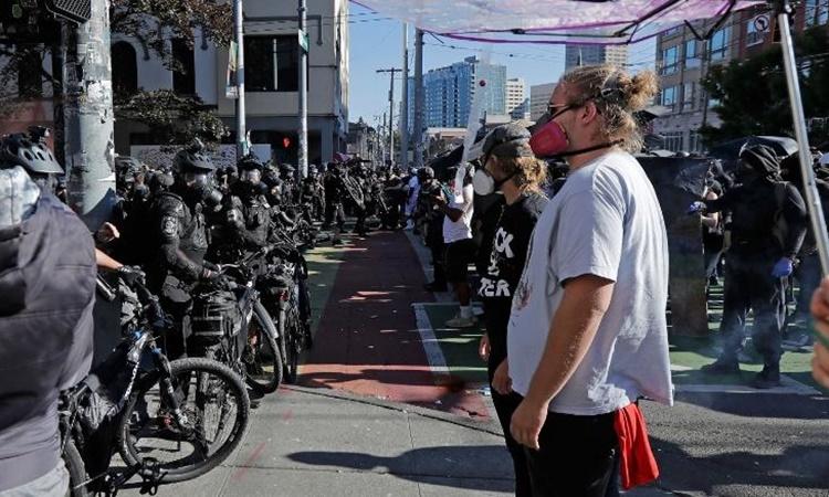 Cảnh sát dàn hàng, đối mặt người biểu tình ở thành phố Seattle, bang Washington, ngày 25/7. Ảnh: AP.