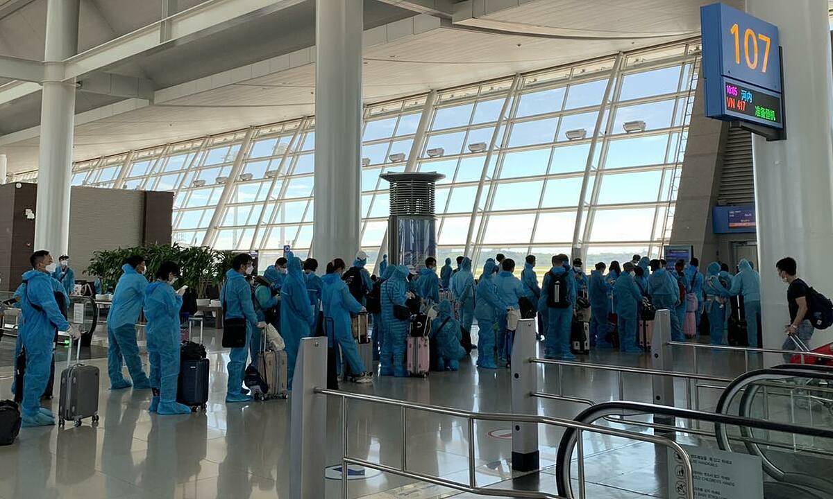 Công dân Việt Nam mặc đồ bảo hộ, xếp hàng tại sân bay ở Hàn Quốc, chờ lên chuyến bay về nước, ngày 26/7. Ảnh: Bộ Ngoại giao.
