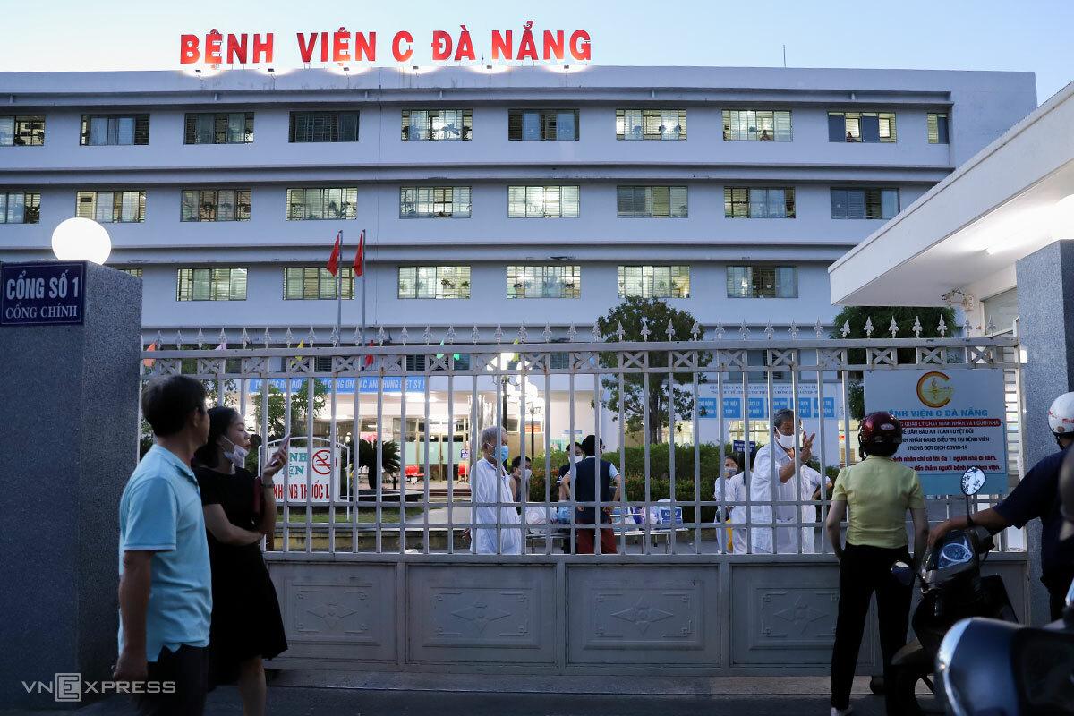 Người thân và bệnh nhân Bệnh viện C phải đưa vật dụng, nói chuyện với nhau qua cánh cổng vì phải phong toả từ ngày 25/7. Ảnh: Nguyễn Đông.