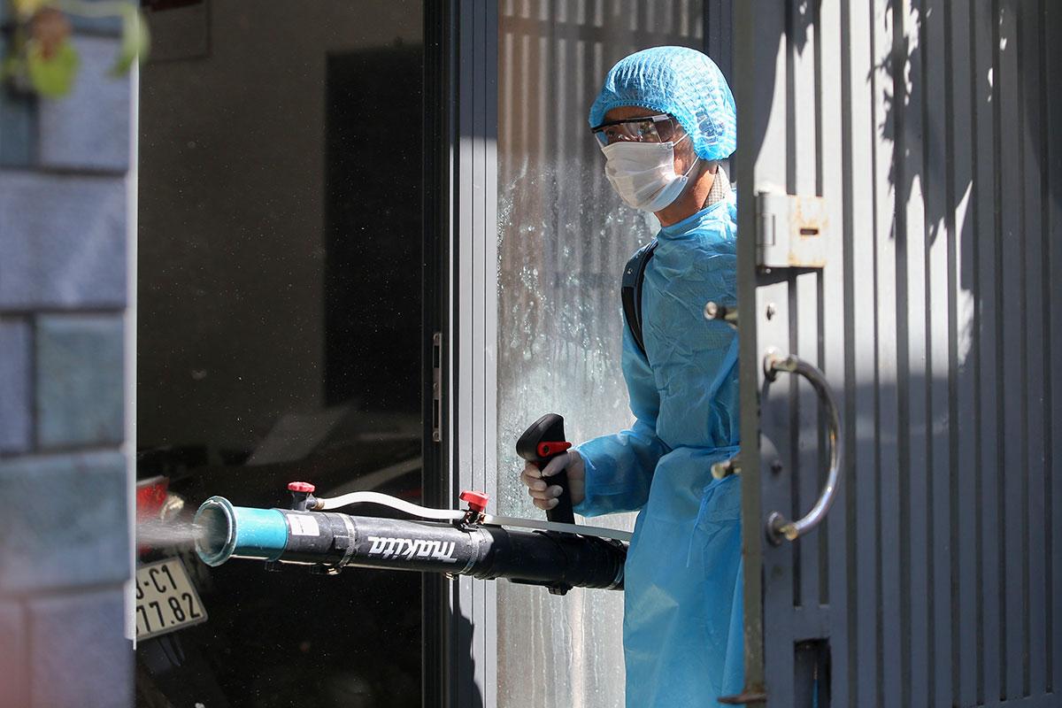 Nhân viên y tế phun thuốc tại nơi ở của bệnh nhân, sáng 26/7. Ảnh: Đắc Thành.