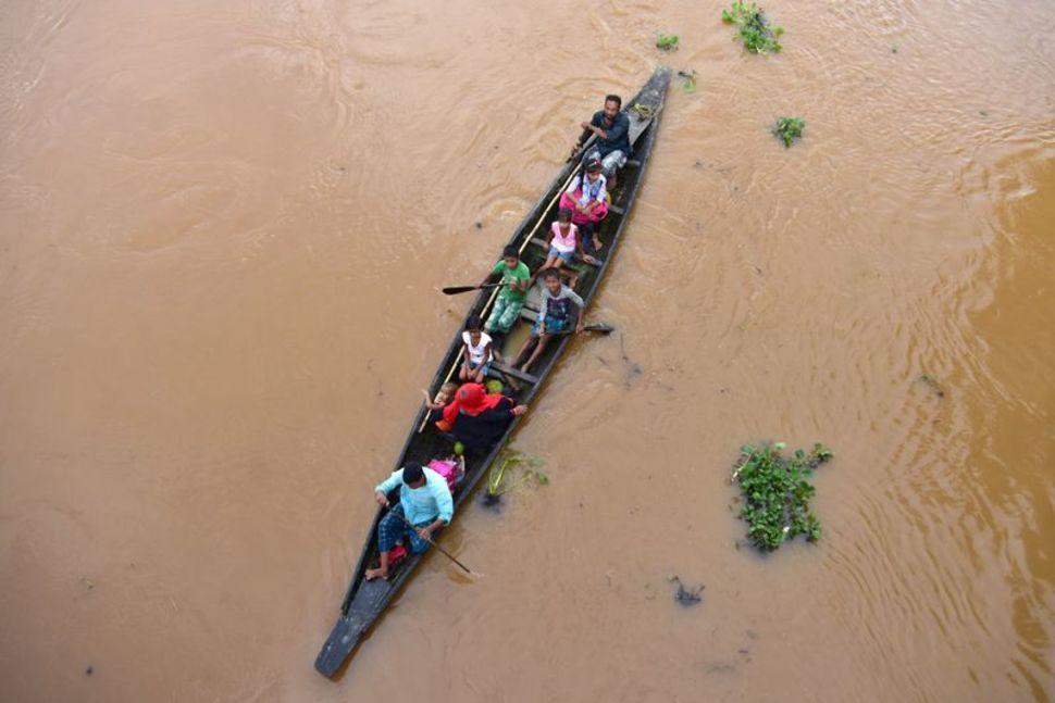 Người dân bị lũ ảnh hưởng tại làng Lachua, huyện Nagaon, bang Assam, được thuyền đưa tới nơi an toàn hôm 22/7, Ảnh: Reuters.