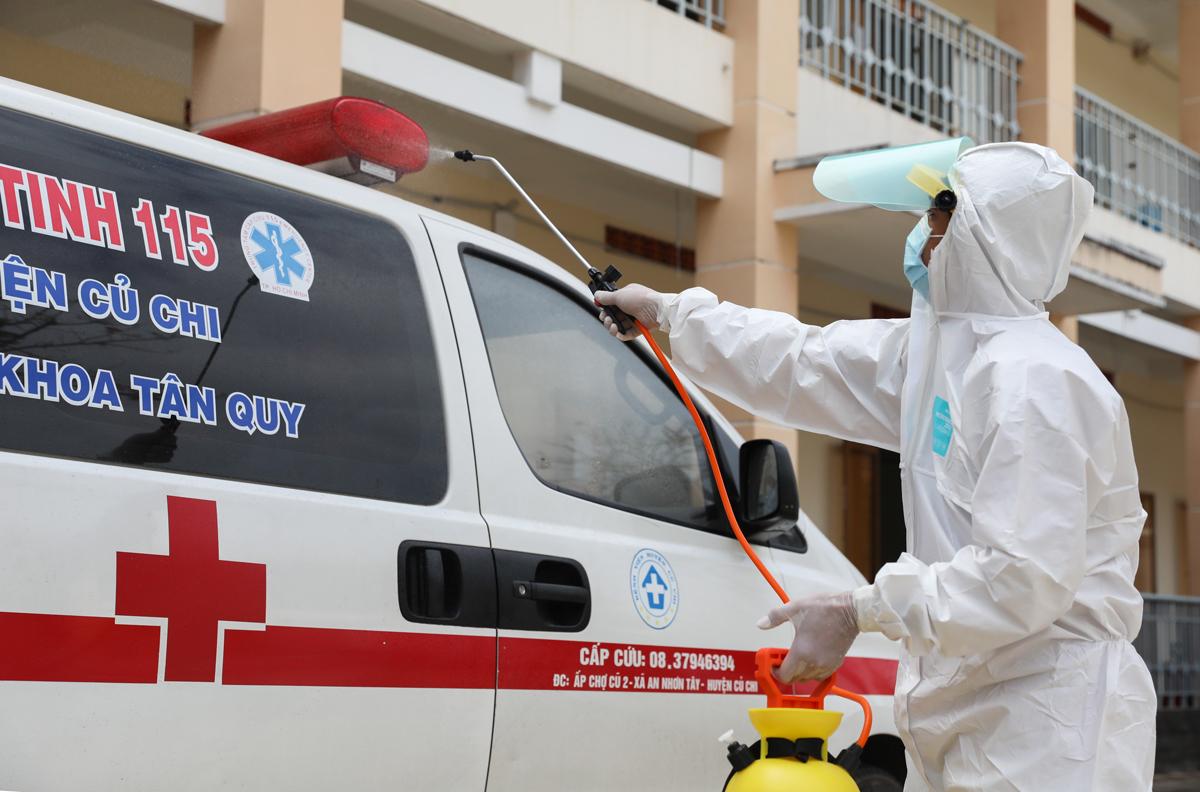 Nhân viên y tế khử trùng xe cấp cứu đưa người đến cách ly tại Bệnh viện dã chiến Củ Chi hồi tháng 2. Ảnh: Quỳnh Trần.