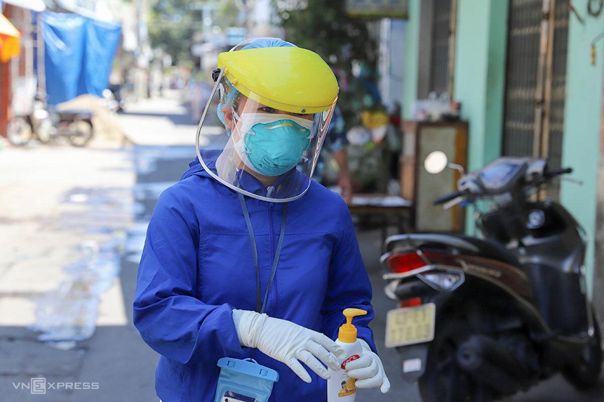 Nhân viên y tế ở Đà Nẵng đi nhắc nhở người dân đeo khẩu trang, sát khuẩn để phòng chống dịch. Ảnh: Nguyễn Đông.