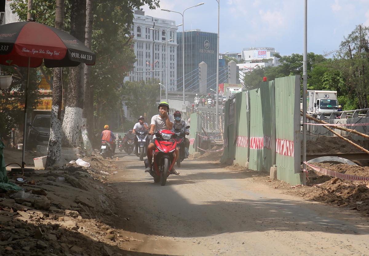 Đường Nguyễn Hữu Cảnh bên hông cầu vượt, rào chắn thi công chiếm hơn nửa mặt đường, đất cát đọng bụi mù mịt khiến các loại xe di chuyển khó khăn, trưa 29/7. Ảnh: Hạ Giang.