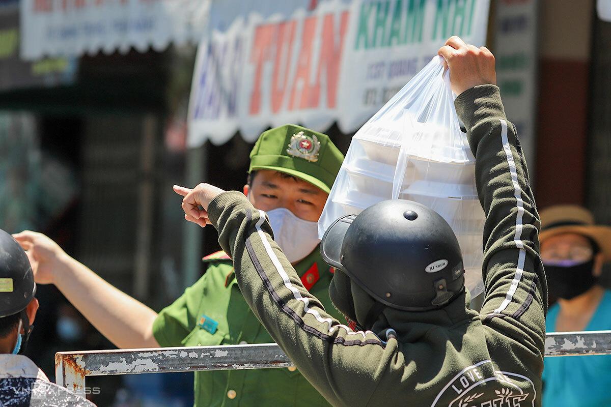 Người nhà mua thức ăn bán mang đi gửi vào cho bệnh nhân tại Bệnh viện Đà Nẵng đang phải cách ly, trưa 29/7. Ảnh: Nguyễn Đông.