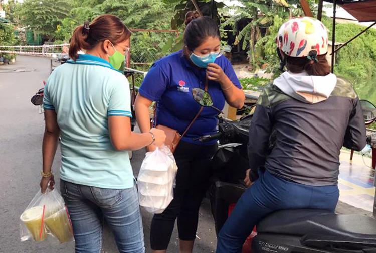 Khi người thân tiếp tế thức ăn, nước uống, cán bộ phường nhận rồi đưa vào cho người bị cách ly. Ảnh: Đinh Văn.