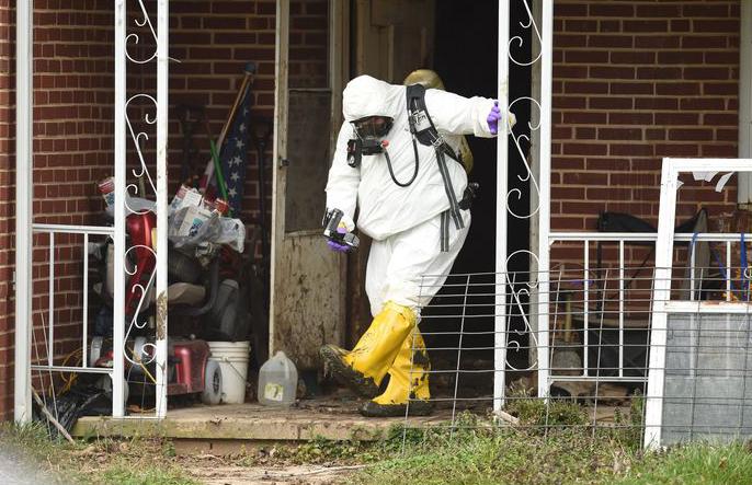 Lực lượng chức nâng mặc đồ bảo hộ trong lúc khám nhà. Ảnh: Carrol County Times.