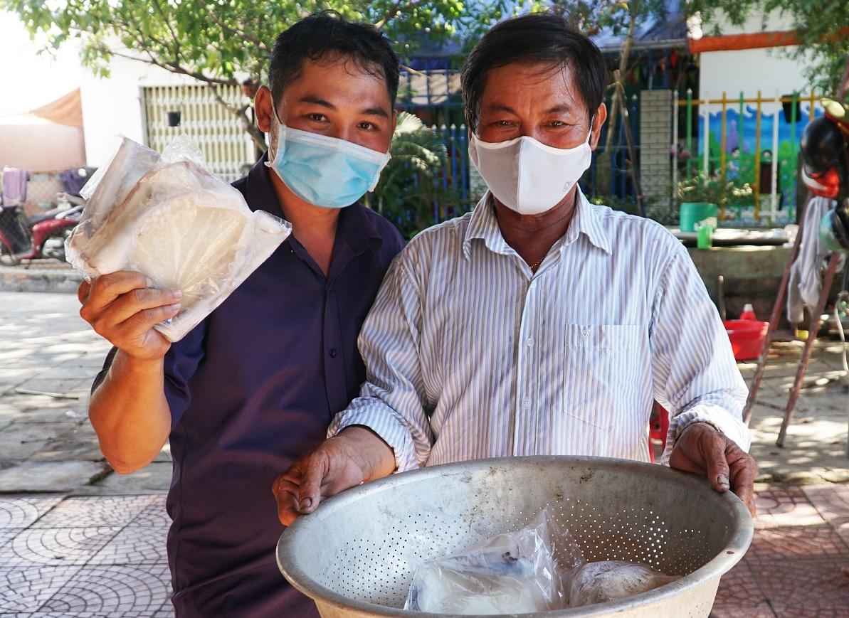 Anh Dương Duy Din, trưởng thôn Hải Ninh mua 300.000 mực tươi ông Anh (phải) chuẩn bị cho đám cưới con trai. Ảnh: Phạm Linh.