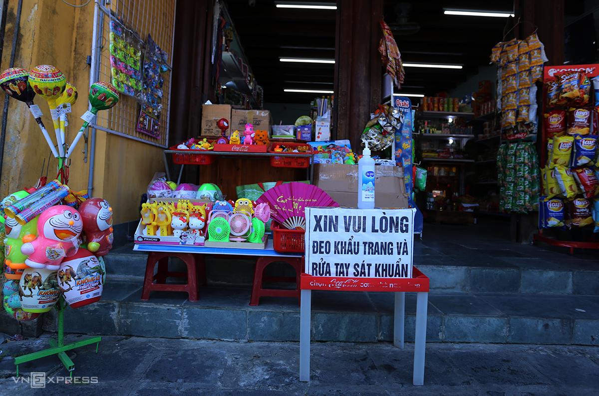 Một cửa hàng yêu cầu khách vào mua hàng đeo khẩu trang, rửa tay sát khuẩn trê đường trần Quý Cáp, TP Hội An chiều 29/7. Ảnh: Đắc Thành.