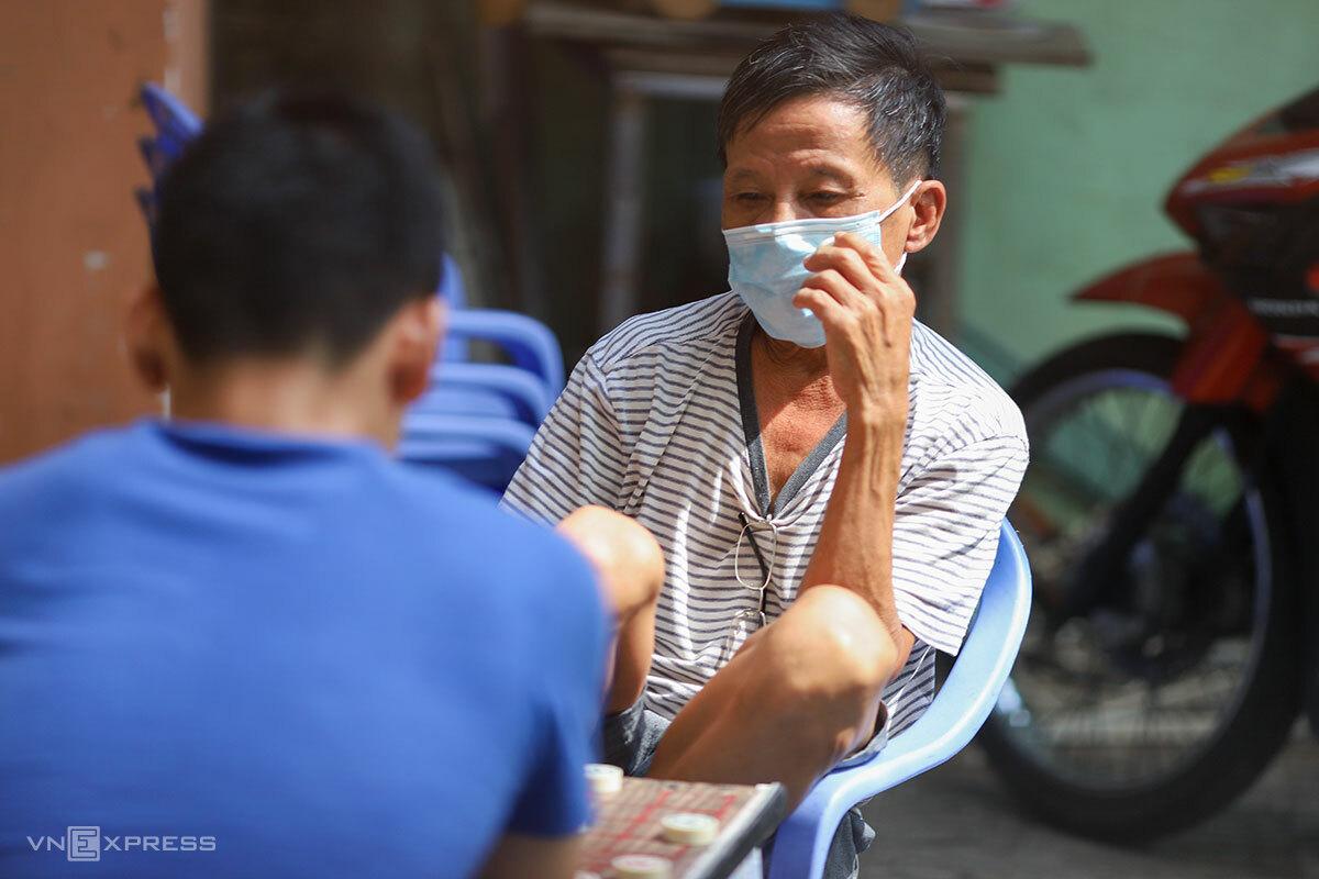 Người dân Đà Nẵng chấp hành đeo khẩu trang, khi chơi cờ ngay trước cổng nhà, sáng 30/7. Ảnh: Nguyễn Đông.