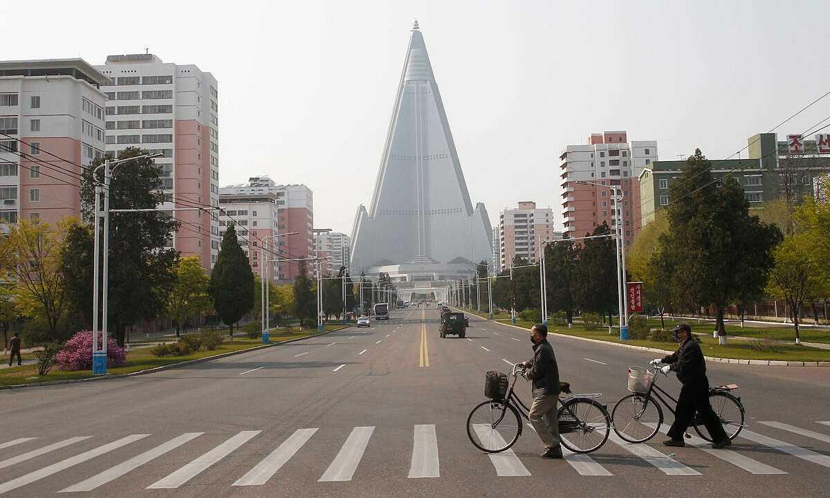 Người dân đeo khẩu trang băng qua một con đường trước khách sạn Ryugyong ở thủ đô Bình Nhưỡng, Triều Tiên, ngày 28/4. Ảnh: AP.