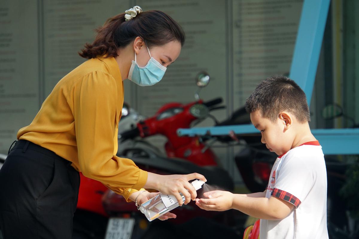 Giáo viên trường Mầm non Hoa Phượng Đỏ (quận Gò Vấp) giúp trẻ rửa tay trước khi vào lớp ngày 18/5. Ảnh: Mạnh Tùng.