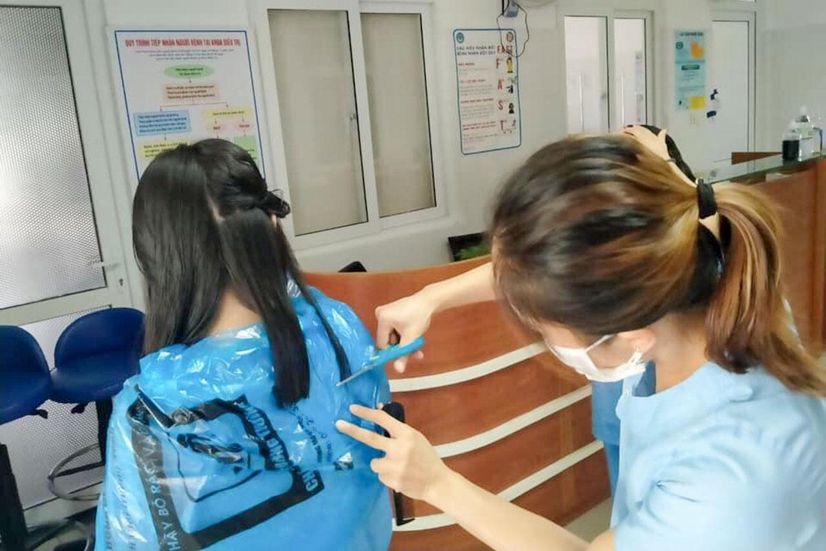 Nhân viên Bệnh viện Đà Nẵng cắt tóc cho nhau để tiện cho việc mang đồ bảo hộ và chăm sóc người bệnh. Ảnh: Hà Thu.