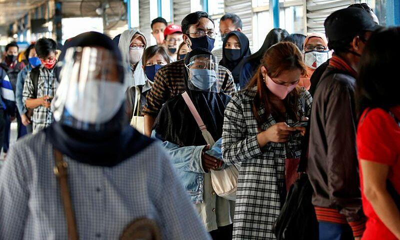 Người dân đeo khẩu trang và tấm chắn giọt bắn khi xếp hàng chờ xe buýt ở trung tâm thủ đô Jakarta, Indonesia, hôm 27/7. Ảnh: Reuters.