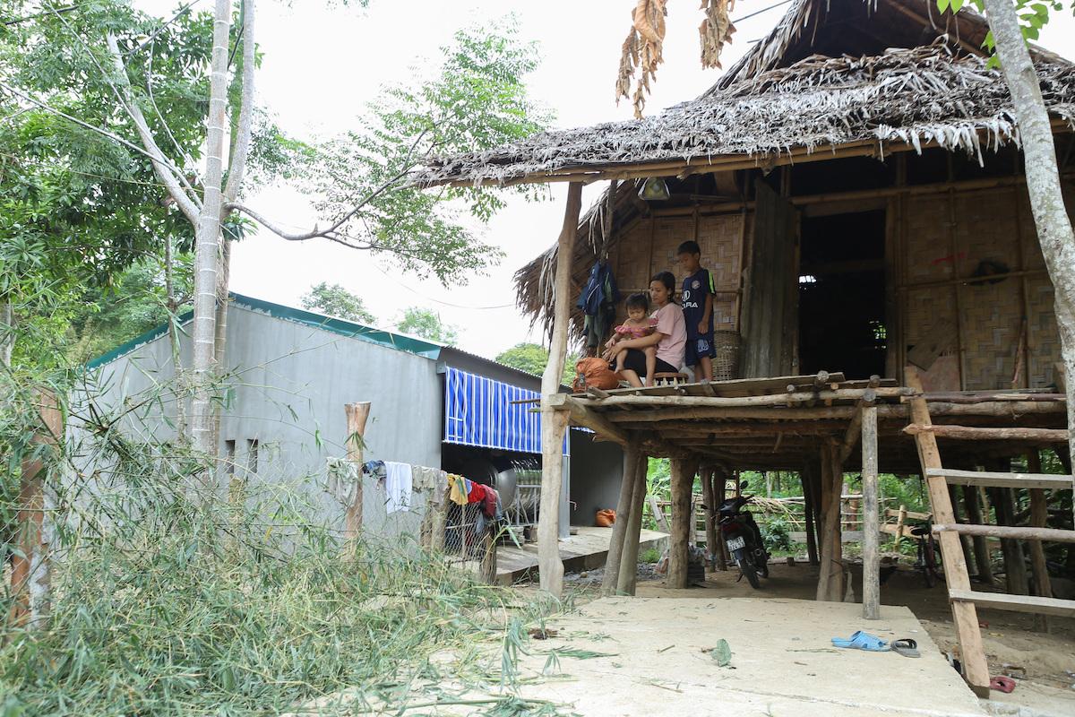 Chuồng bò xây gạch, lợp mái tôn (màu xanh) nằm bên cạnh một nhà dân đang mái tranh ở bản Văng Môn. Ảnh: Nguyễn Hải.
