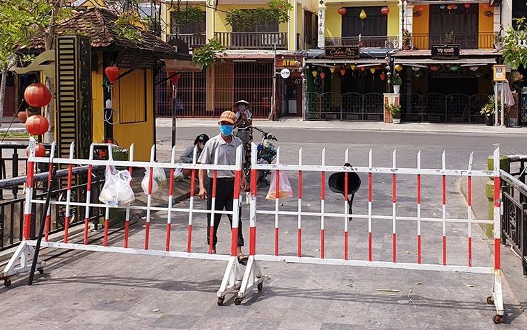 Người dân ở Hội An ra khu vực hàng rào phong tỏa khối phố An Hội, phường Minh An nhận thực phẩm. Ảnh: Đắc Thành.