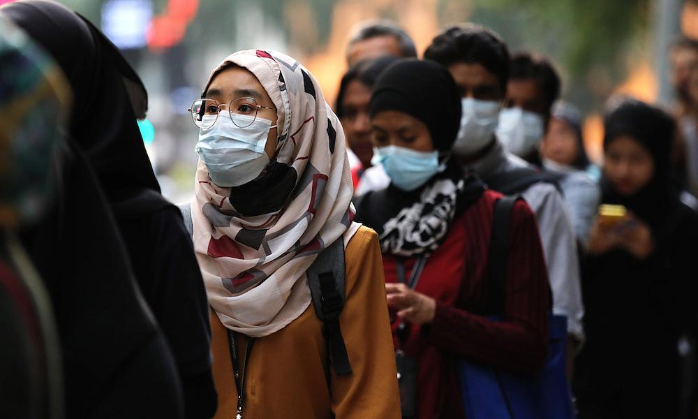 Người Malaysia đeo khẩu trang khi xếp hàng tại một trạm xe buýt ở Kuala Lumpur, ngày 31/1. Ảnh: Reuters.