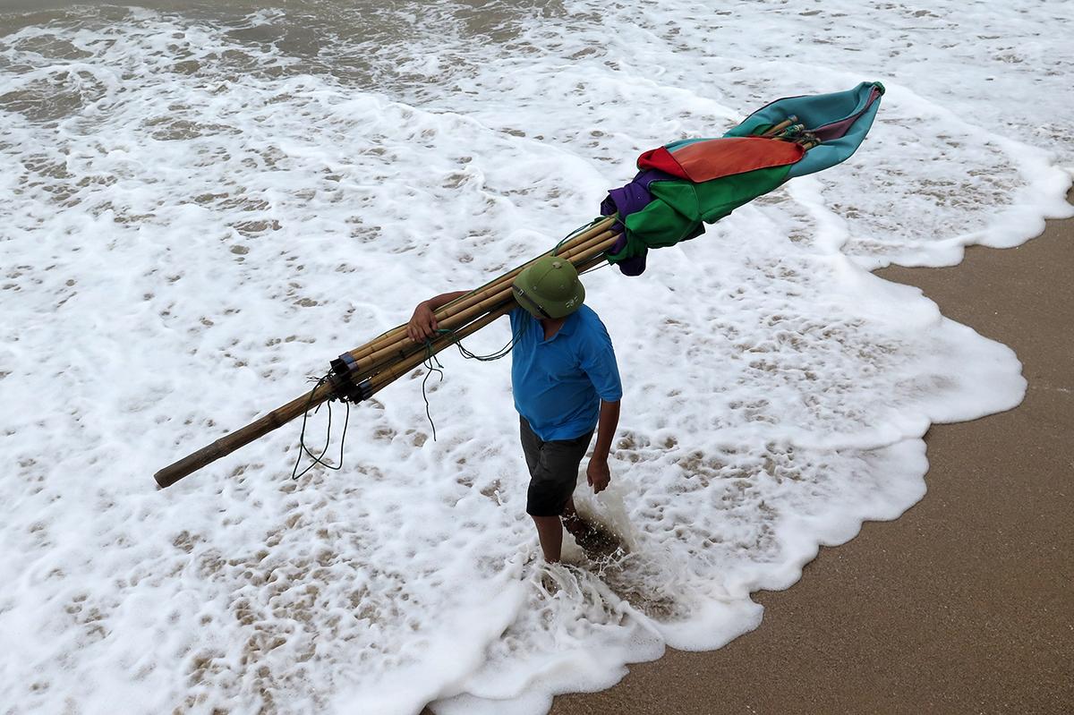 Người dân thu dọn ô dù trên bãi tắm khu 2 mang lên bờ cất, chống bão. Ảnh: Giang Chinh