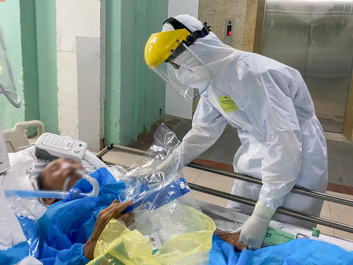 Nhân viên y tế thay người nhà chăm sóc cho bệnh nhân tại Bệnh viện Đà Nẵng. Ảnh: Minh An.