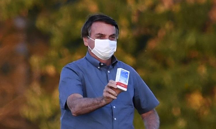Tổng thống Brazil giơ hộp thuốc chống sốt rét hydroxychloroquine trước những người ủng hộ ở thủ đô Brasilia hôm 23/7. Ảnh: AFP.
