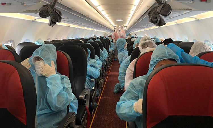 Hành khách và thành viên phi hành đoàn mặc trang phục bảo hộ, đeo khẩu trang trên chuyến bay hồi hương hơn 230 công dân từ Thái Lan, ngày 2/8. Ảnh: Bộ Ngoại giao.