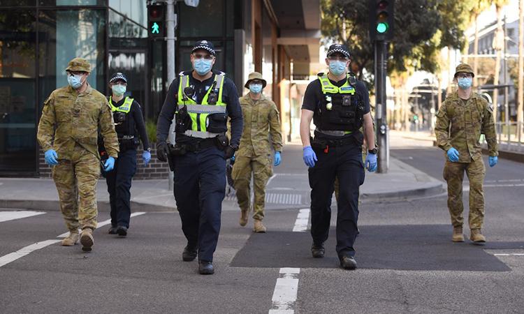 Nhóm cảnh sát và binh sĩ đi tuần sau tại khu vực Docklands, Melbourne, sau khi giới chức bang Victoria của Australia ban hành lệnh hạn chế ngăn nCoV mới, ngày 2/8. Ảnh: AFP.