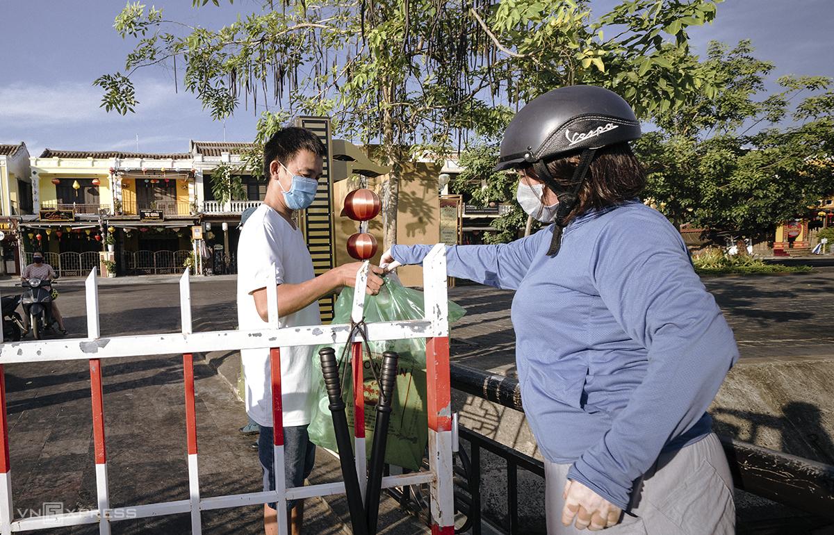 Người dân khối phố An Hội, phường Minh An, thành phố Hội An lấy thực phẩm qua hàng rào phong tỏa sáng 30/7. Ảnh: Trí Lê.