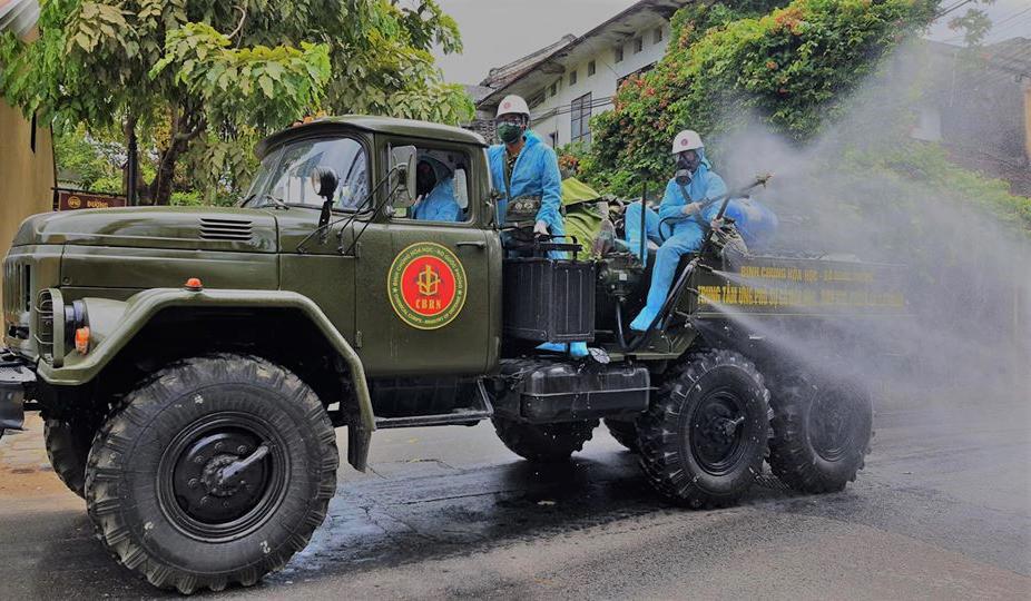 Lực lượng quân sự phun hóa chất khử trùng trên các tuyến đường phố cổ Hội An, sáng 2/8. Ảnh: Đại Chí.