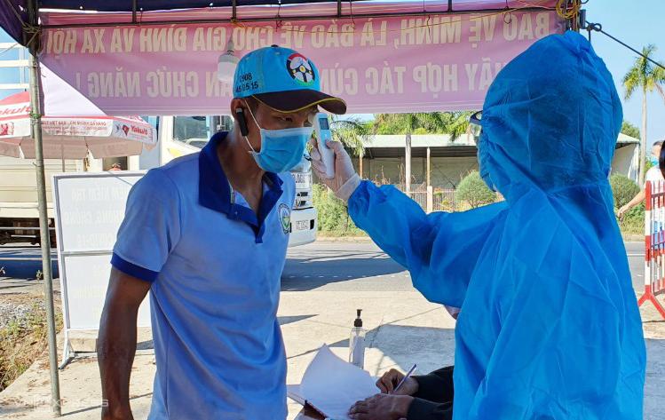Nhân viên y tế đo thân nhiệt tại chốt trên đường cao tốc Đà Nẵng - Quanrng Ngãi xuống huyện Thăng Bình. Ảnh: Đắc Thành.
