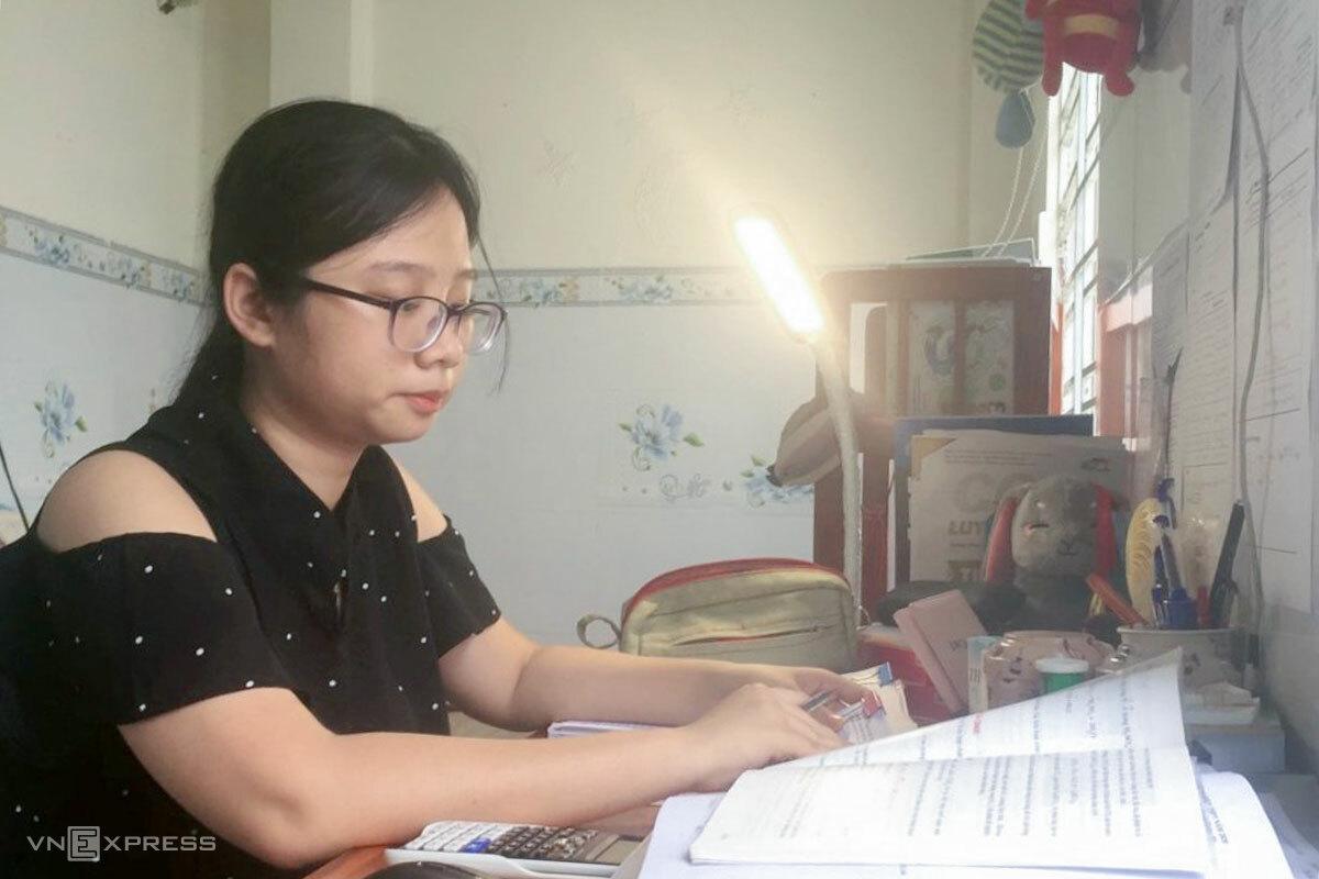 Minh An học bài sau khi thay mẹ làm việc nhà. Ảnh: Anh Tuấn.