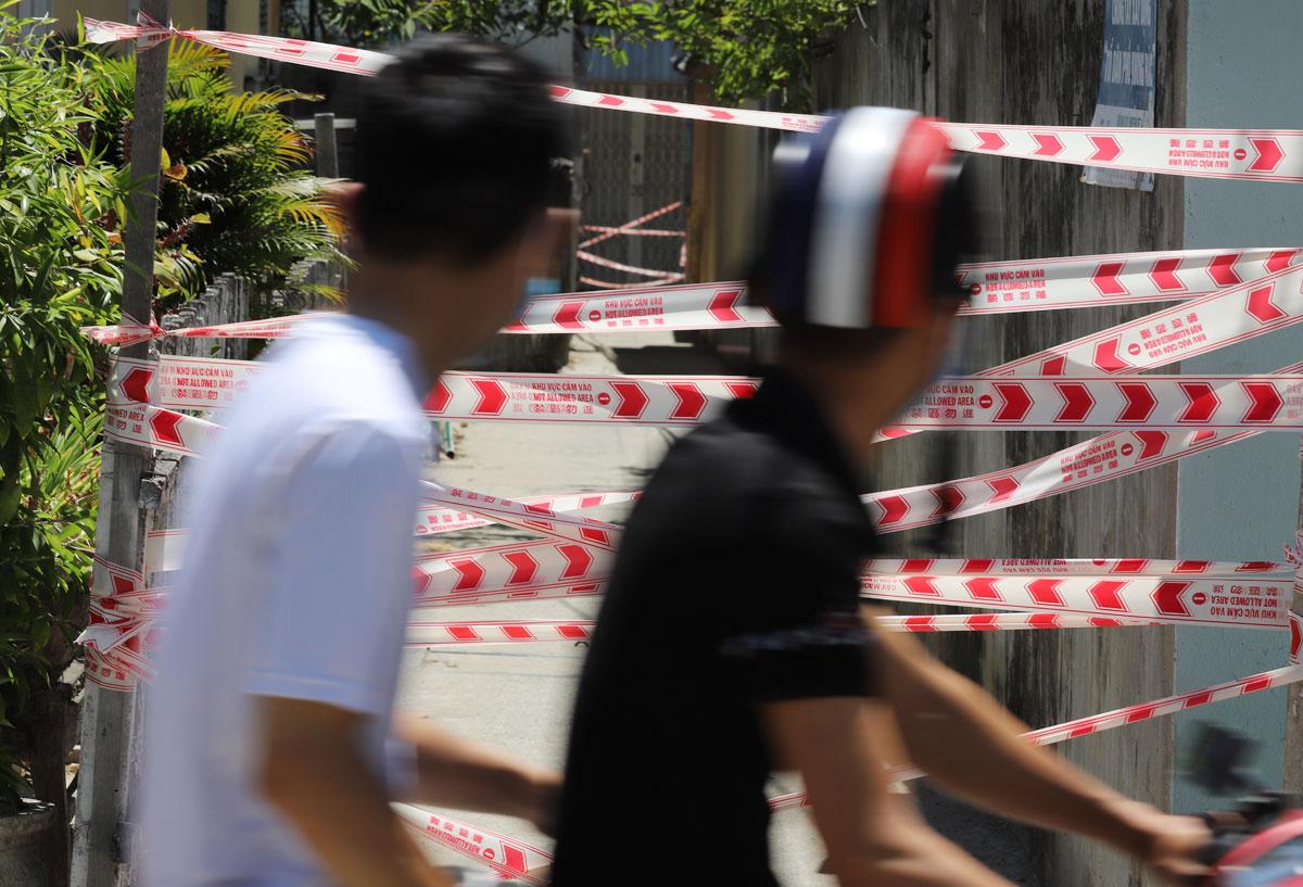 Người dân đi ngang một khu dân cư bị phong toả vì có người mắc nCoV, ngày 28/7. Ảnh: Nguyễn Đông