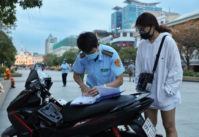 Đội trật tự đô thị phường Bến Nghé, quận 1, xử phạt người không đeo khẩu trang trên phố đi bộ Nguyễn Huệ, chiều 15/4. Ảnh: Quỳnh Trần.