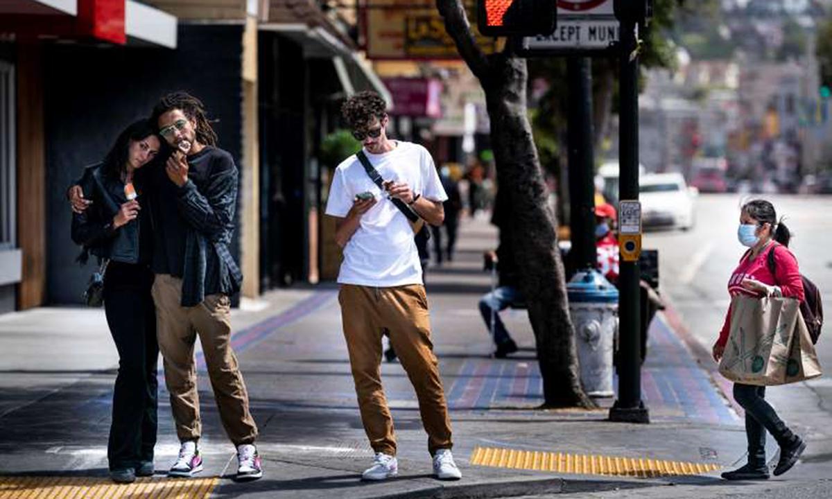 Một số người đi bộ không đeo khẩu trang trên phố Mission, thành phố San Francisco, tháng trước. Ảnh: Washington Post.