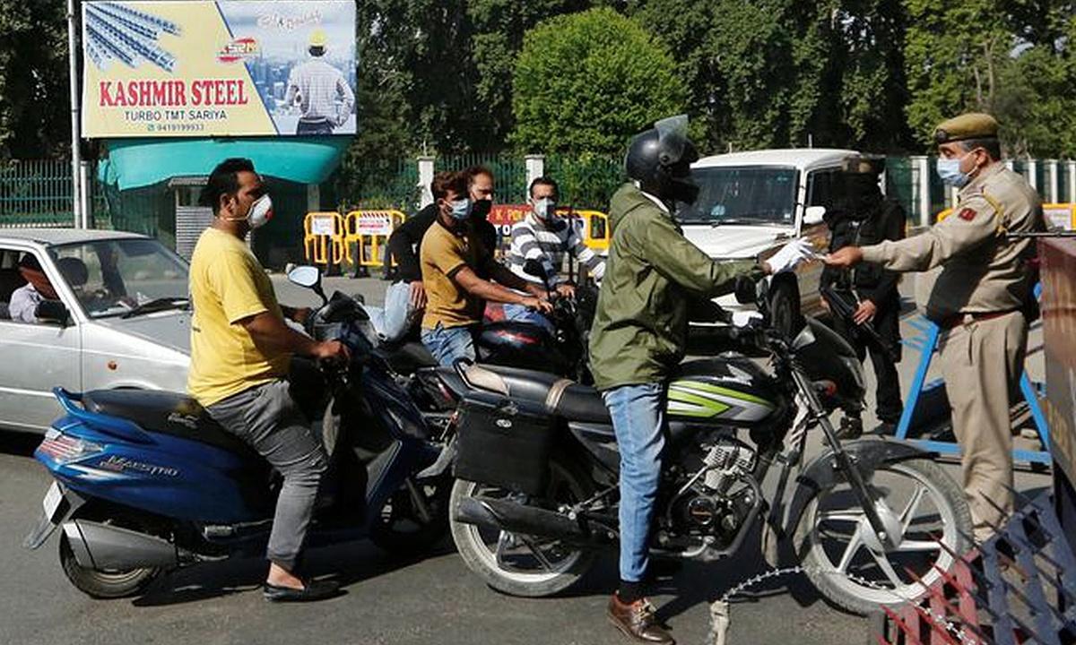 Cảnh sát Ấn Độ kiểm tra giấy tờ tùy thân của người dân tại khu vực hàng rào an ninh, được thiết lập theo lệnh giới nghiêm ở Kashmir, ngày 4/8. Ảnh: Reuters.