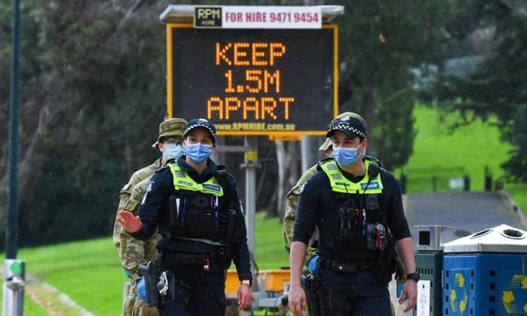 Cảnh sát và binh sĩ làm nhiệm vụ tại một trạm kiểm soát ở Melbourne, Victoria hôm nay. Ảnh: AFP.