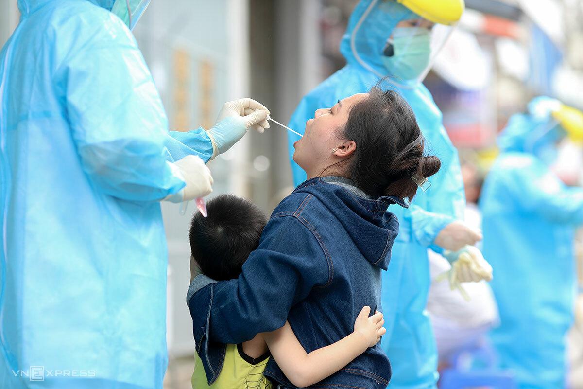 Nhân viên y tế lấy mẫu xét nghiệm tại cộng đồng cho người dân. Ảnh: Nguyễn Đông.