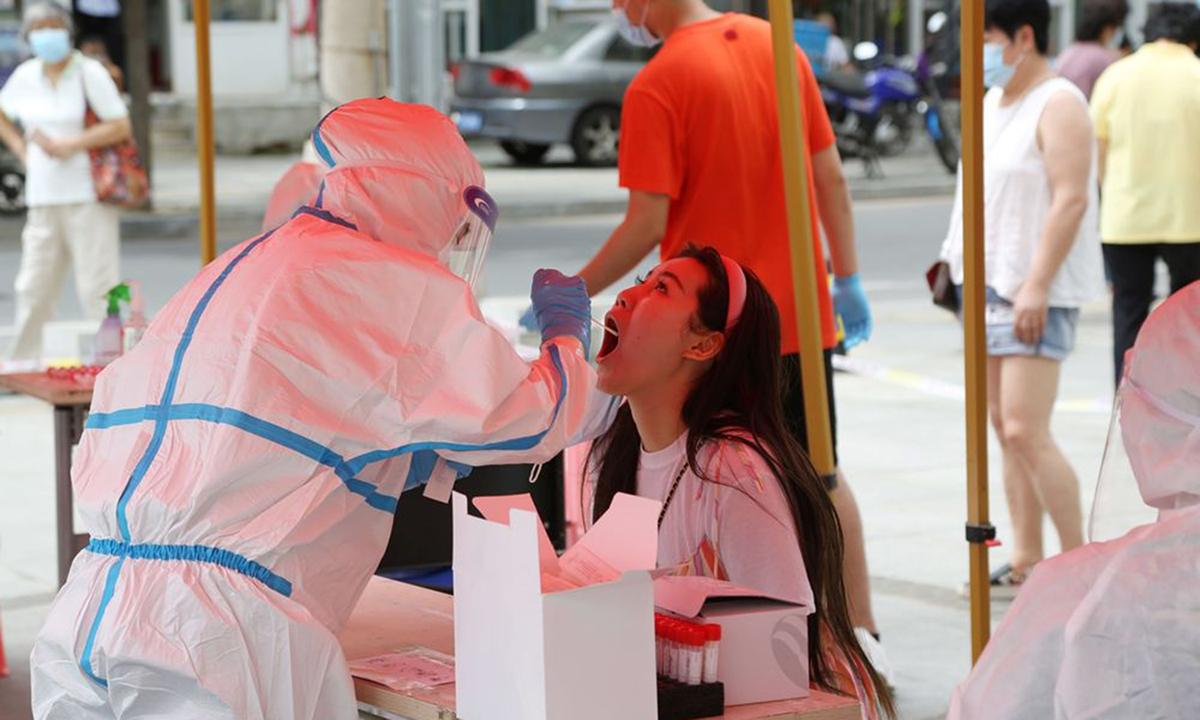Nhân viên y tế lấy mẫu xét nghiệm nCoV tại thành phố Đại Liên, tỉnh Liêu Ninh, hôm 27/7. Ảnh: AFP.