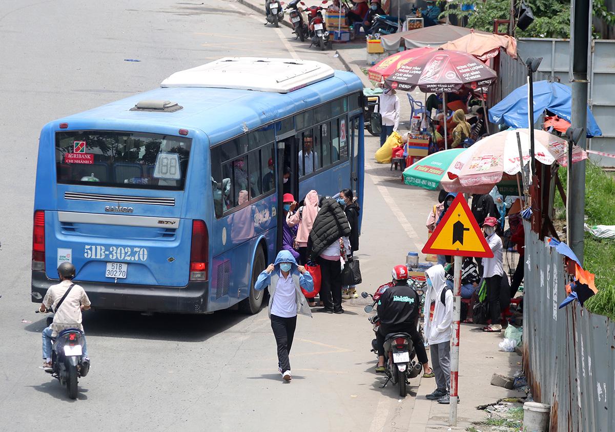 Nhà chờ xe buýt trên quốc lộ 1A đối diện Khu du lịch Suối Tiên (quận 9) bị biến thành nơi kinh doanh, hành khách đứng nắng chờ xe, trưa 5/8. Ảnh: Gia Minh.