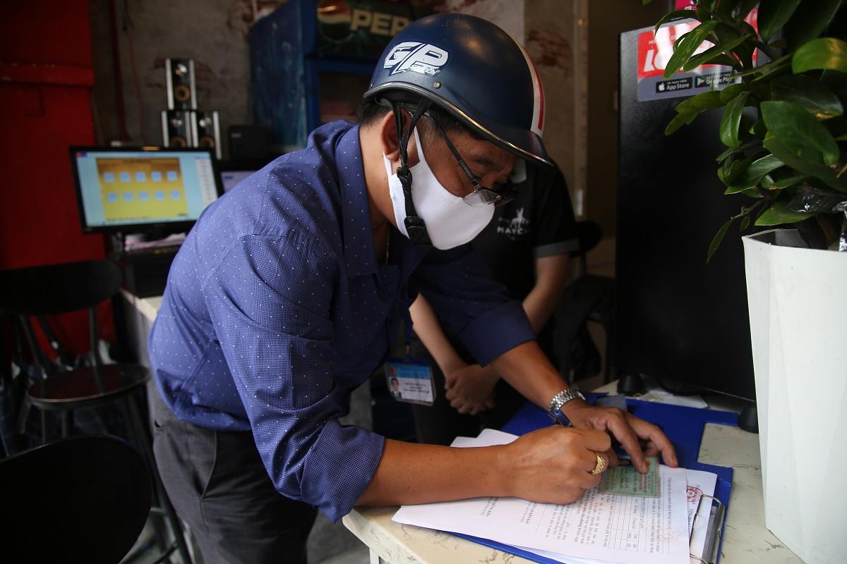 Lực lượng chức năng lập biên bản xử phạt một người không đeo khẩu trang nơi công cộng ở quận 10. Ảnh: Đinh Văn.