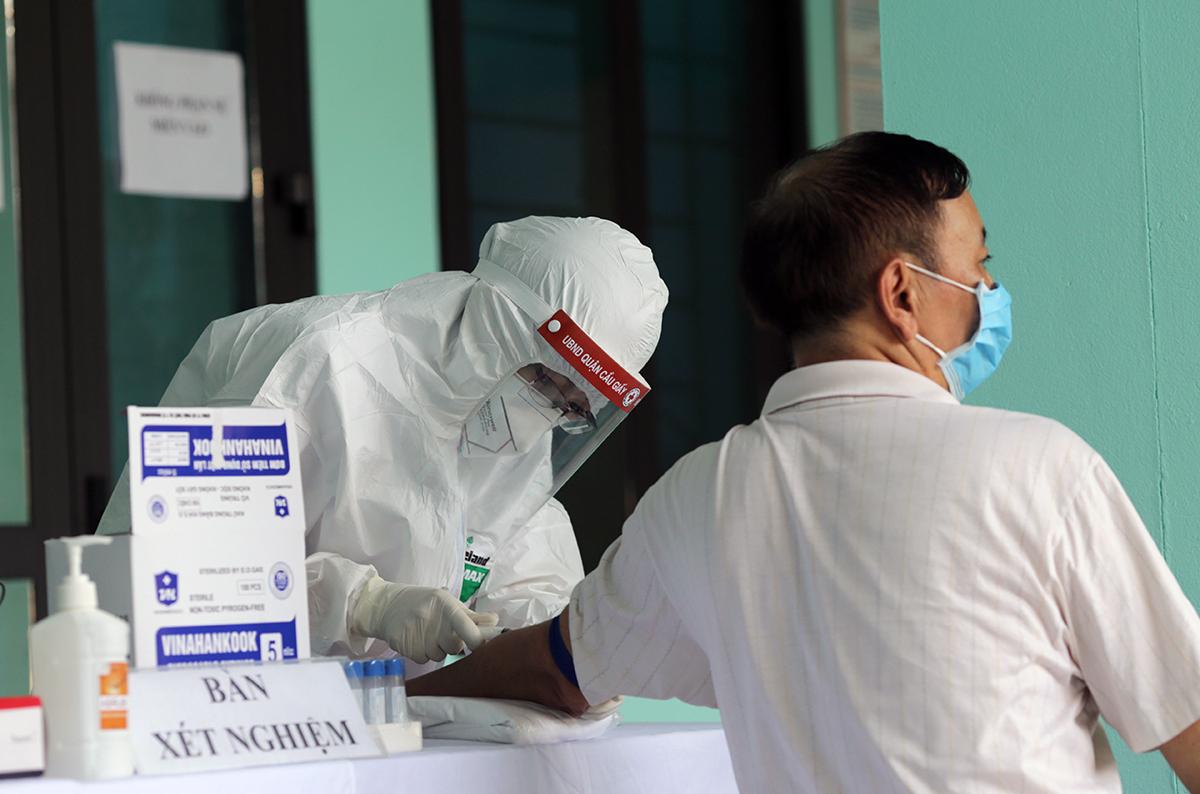 Một người về từ Đà Nẵng về được xét nghiệm test nhanh tại trung tâm y tế phường Yên Hoà, quận Cầu Giấy ngày 30/7. Ảnh: Tất Định.