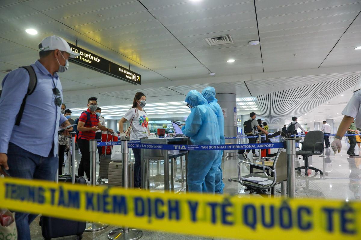 Giám sát tình hình sức khỏe của khách tại sân bay Tân Sơn Nhất ngày 18/3. Ảnh: Hữu Khoa.
