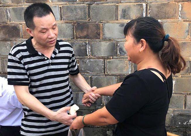 Sau khi được trả tự do vào sáng 4/8, ông Hoàn (trái) gặp lại vợ cũ, người đã ly hôn ông để lập gia đình mới. Ảnh: The Paper.
