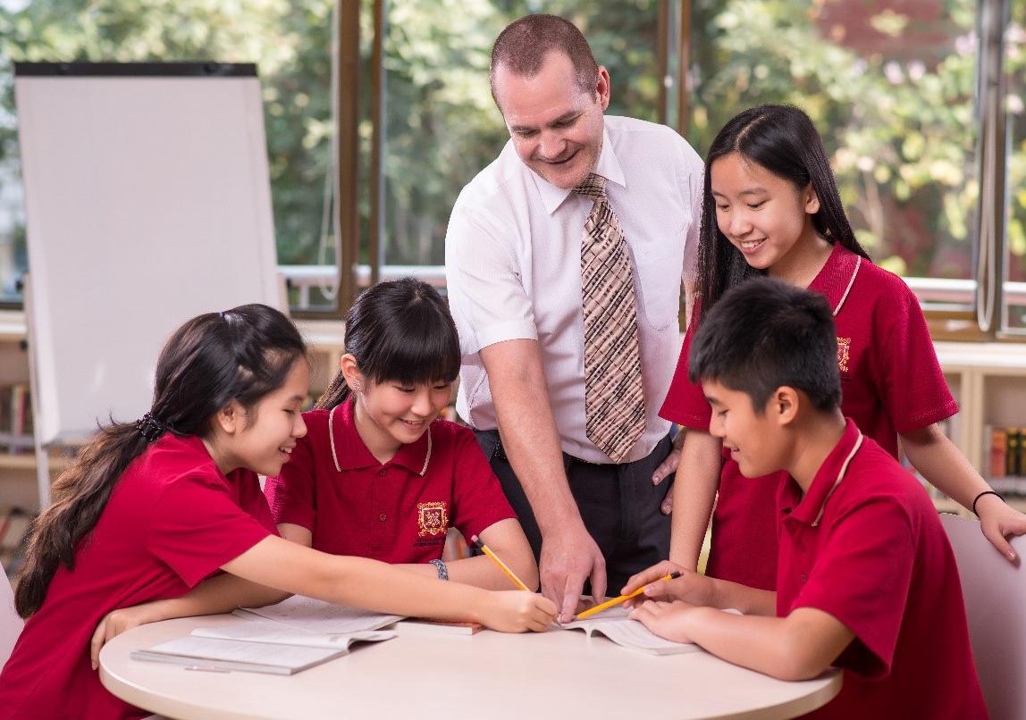 Giáo viên hướng dẫn học sinh thực hành trong môn kinh tế.